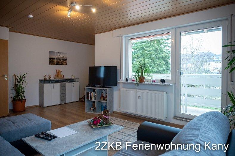 Wohnzimmer mit Sofa, Fernseher und Kommode