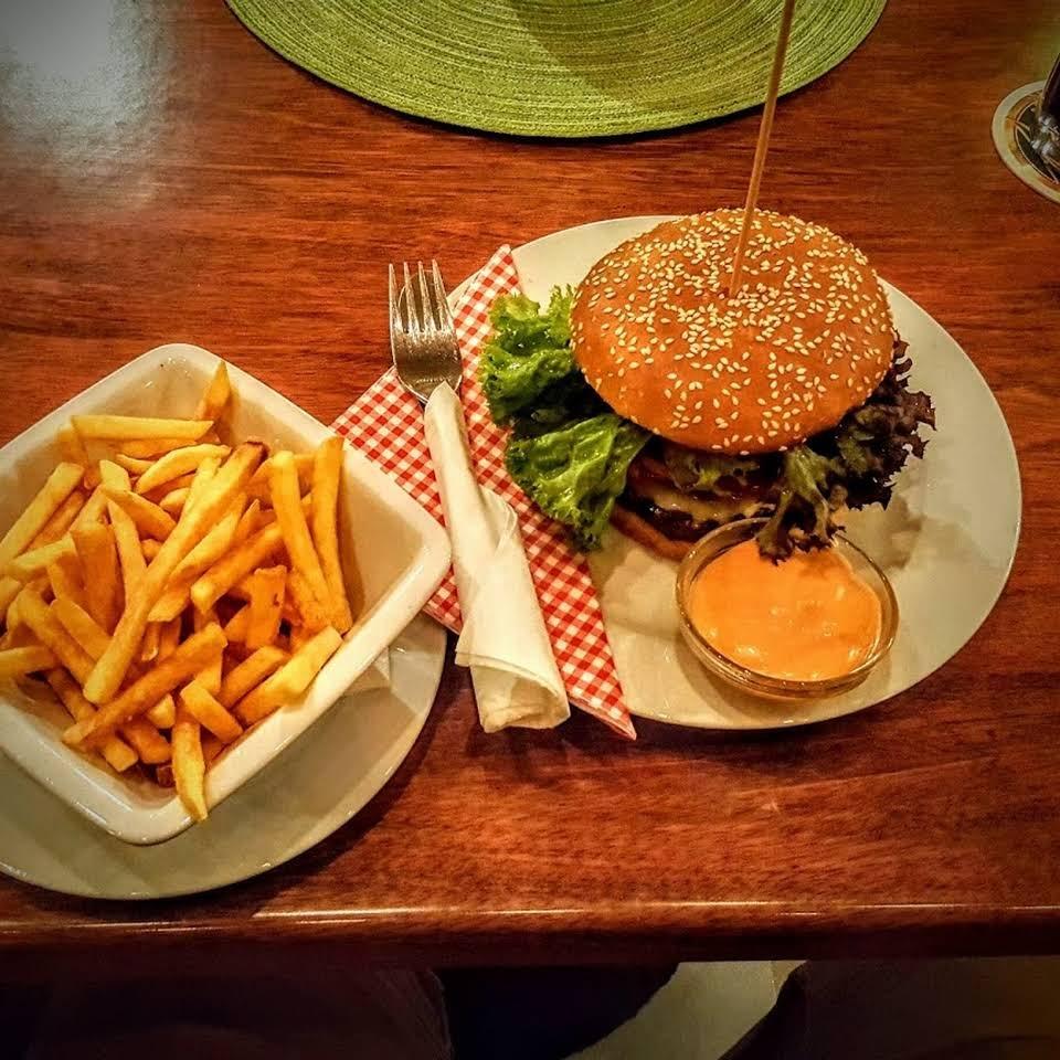 Auf einem Holztische stehen zwei Teller - einer mit einem Burger, der andere mit einer Schale Pommes.