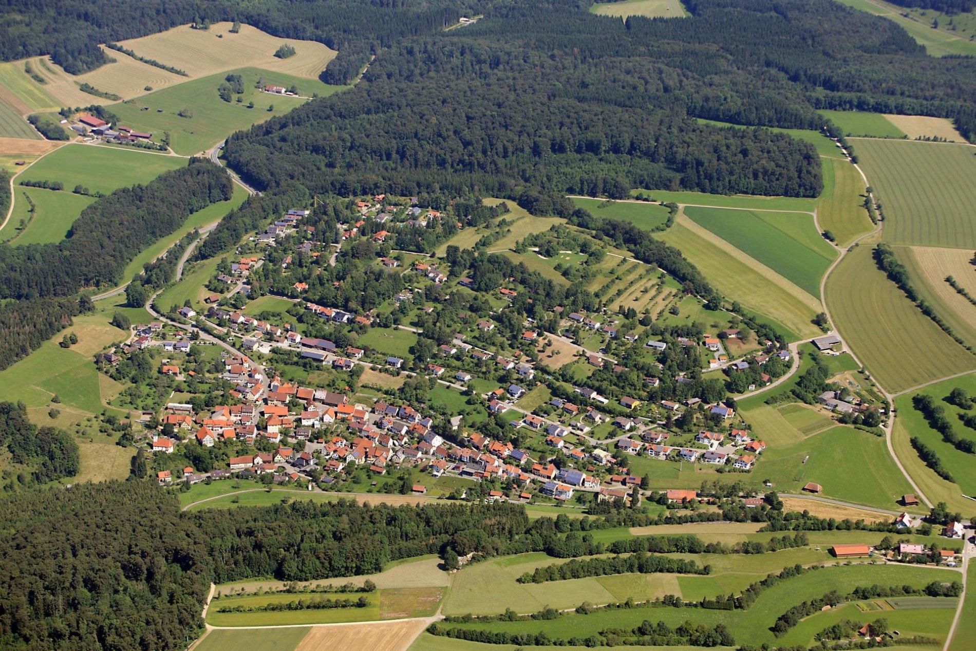 Ein Luftbild von einem Dorf. Ringsherum sind Felder und Wälder.