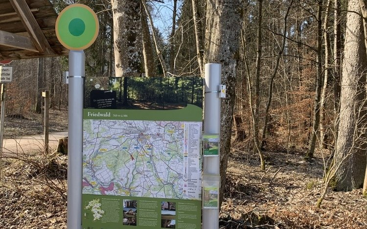 Wanderparkplatzschild mit Prospekthalter und Wegweiser. Im Hintergrund Wald.