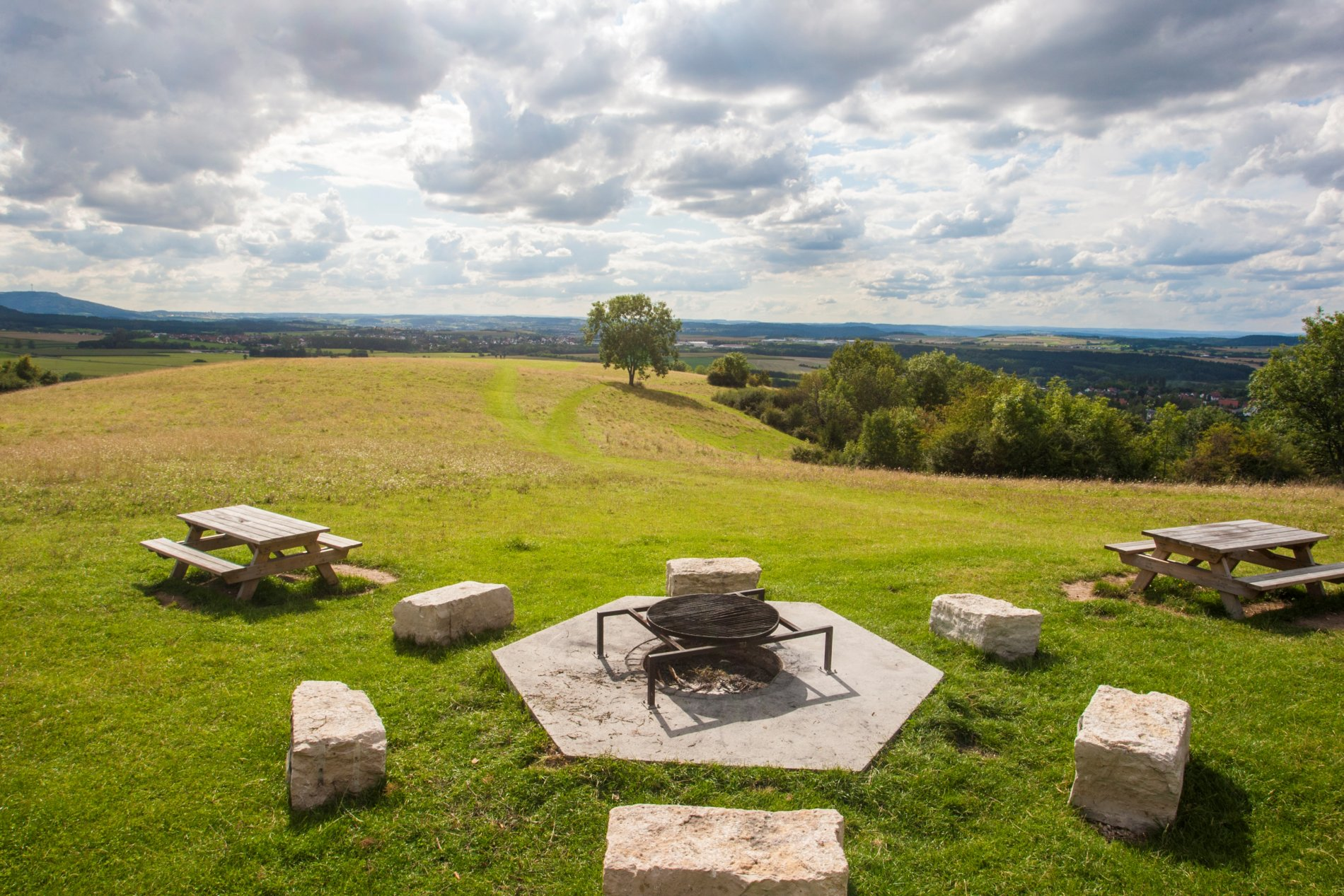 Grillplatz mit Feuerstelle und Sitzmöglichkeiten auf einer Freifläche