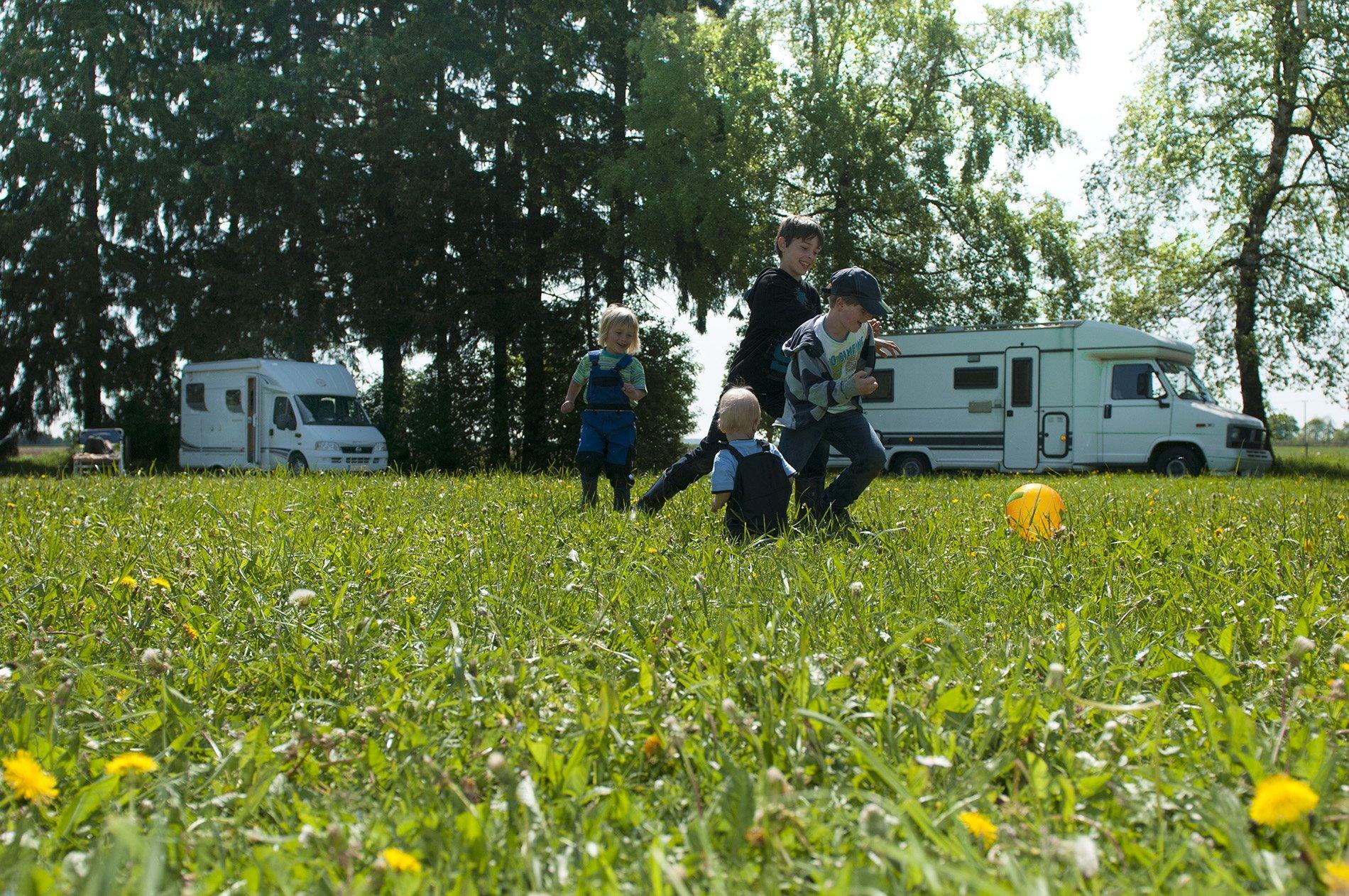 Vier Kinder spielen mit einem Ball auf einer Wiese im Sommer. Im Hintergrund stehen mehrere Wohnmobile unter Bäumen auf einer Wiese.