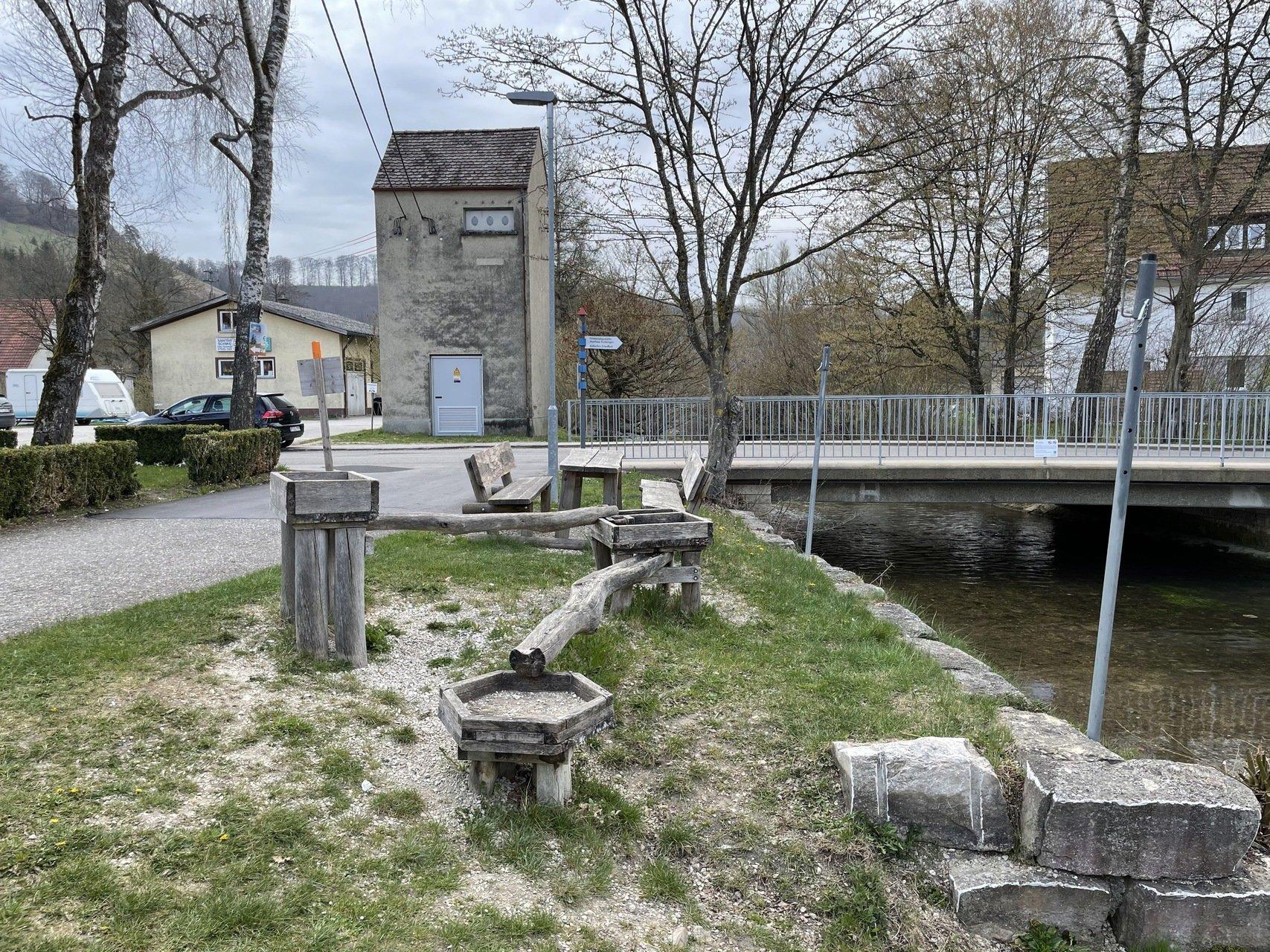 Im Vordergrund ein Wasserspiel aus Holz neben großen Granitsteinen auf der rechten Seite fließt ein Fluß im Hindergrund eine Brücke