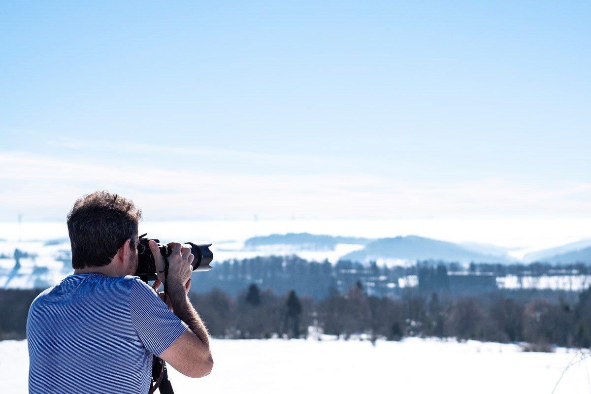 Ein Fotograf mit blauem T-Shirt macht mit seiner Kamera eine Aufnahme von der winterlichen Landschaft
