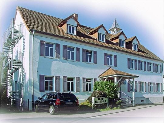 Großes weißes Gebäude mit Fensterläden und braun geziegeltem Dach