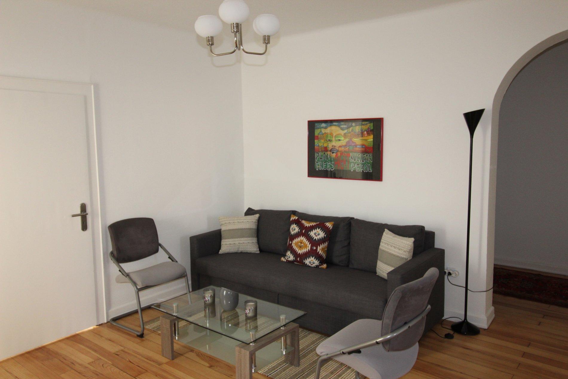 Schwarze Couch mir zwei Stühlen auf Holzboden