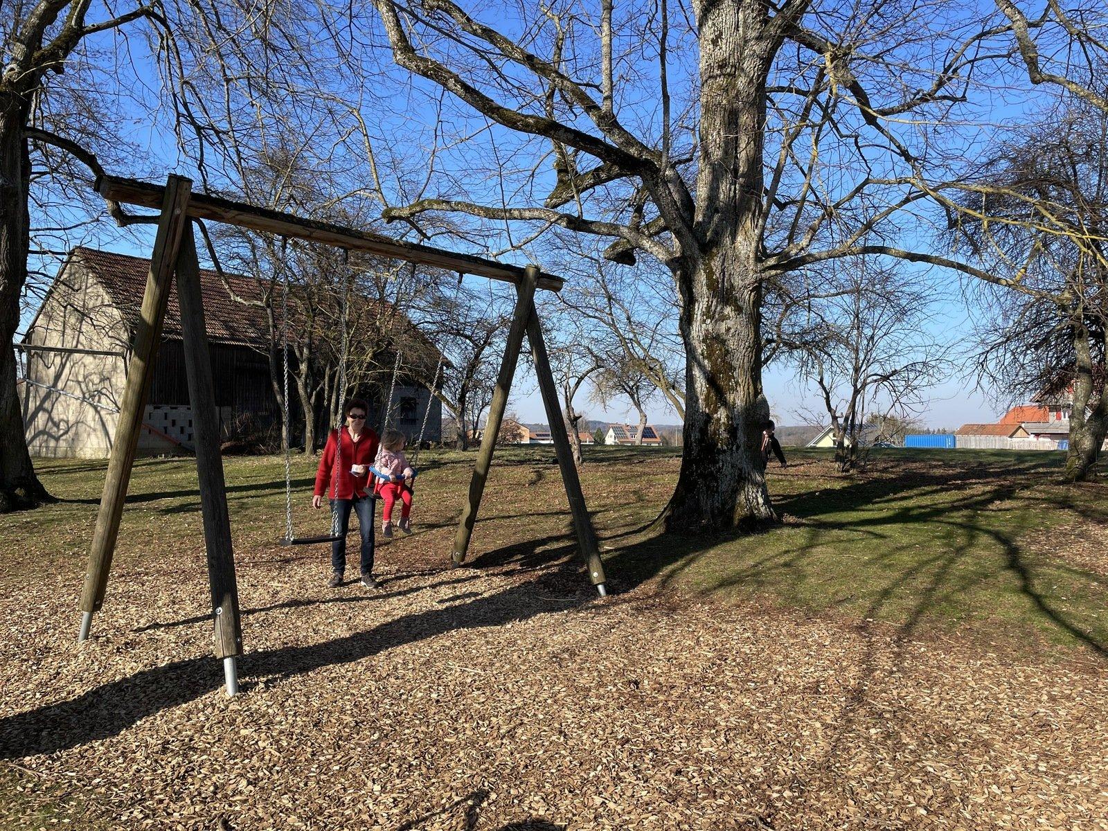 Eine Person mit roter Jacke steht an einer Schaukel und schupst ein Kleinkind auf der Schaukel an