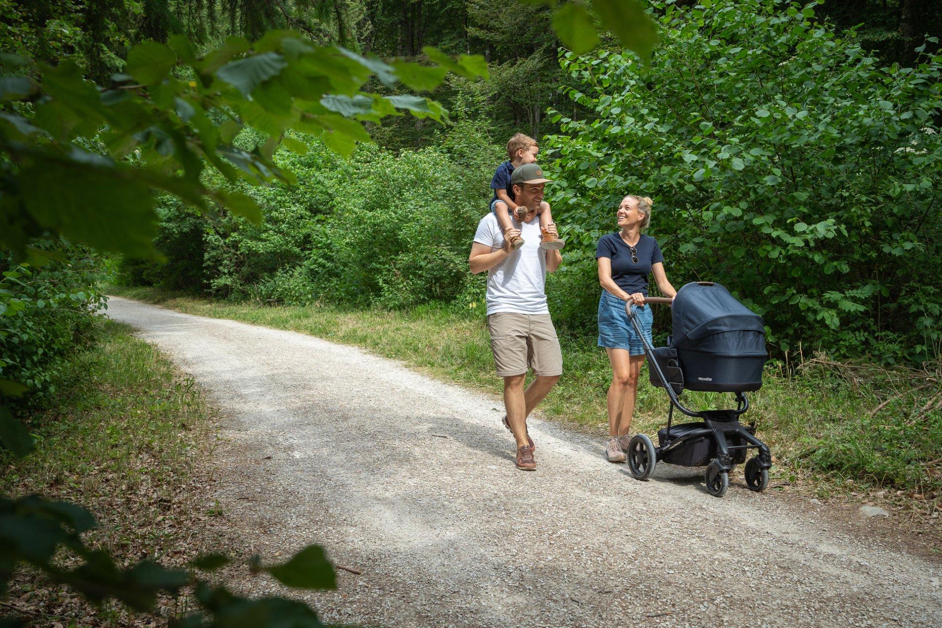 Zwei Wanderer*innen laufen auf einem Wiesenweg lächelnd entlang, der zwischen Hecken und Sträuchern hindurch führt.