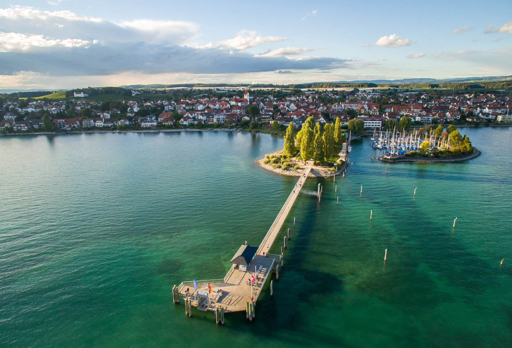 Schiffslandesteg in Immenstaad aus der Luft fotografiert mit türkisfarbenen See darunter und der Ort Immenstaad im Hintergrund