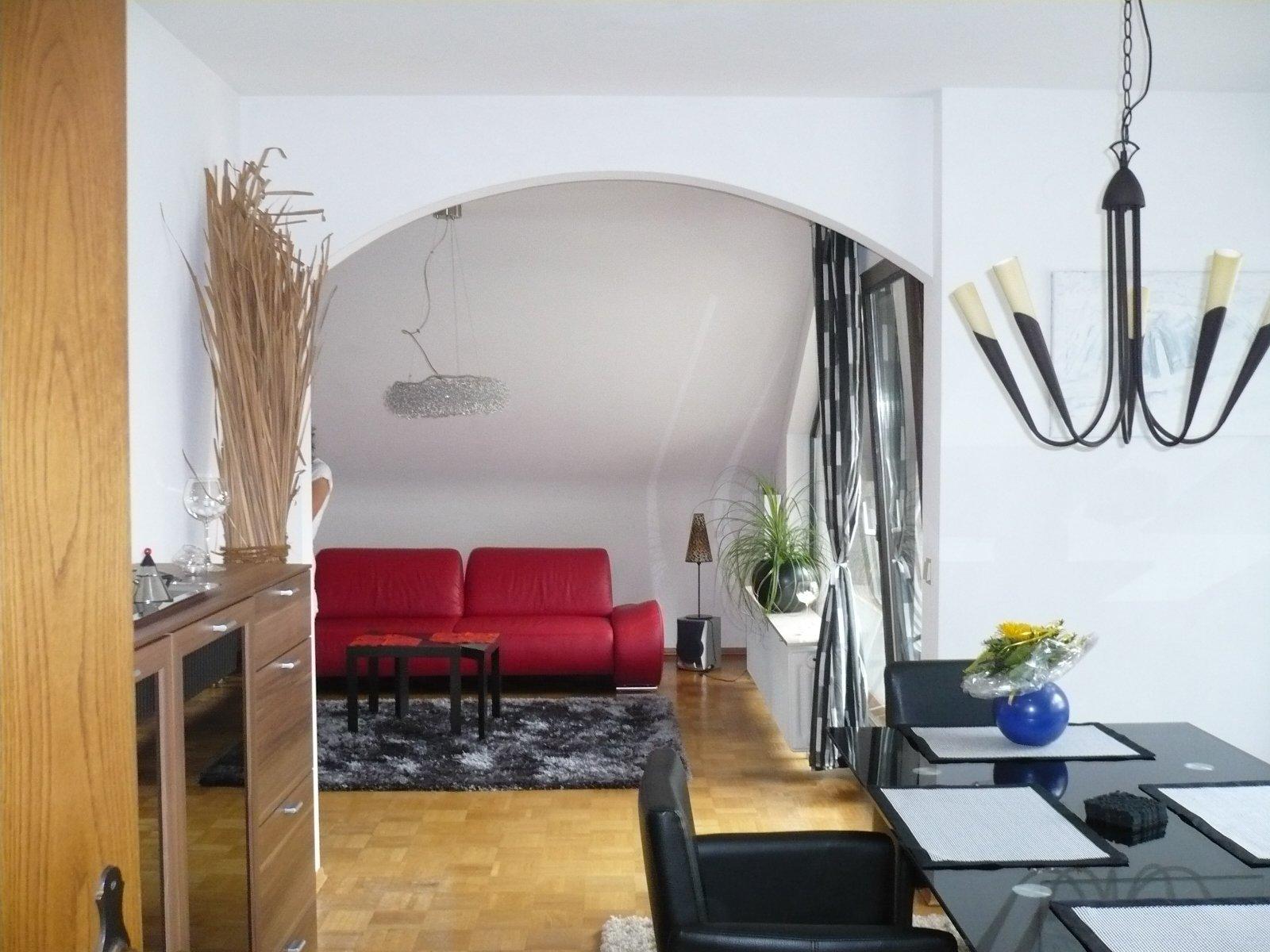 Ess- und Wohnbereich mit Tisch, zwei Stühlen, Kommode und Sofa