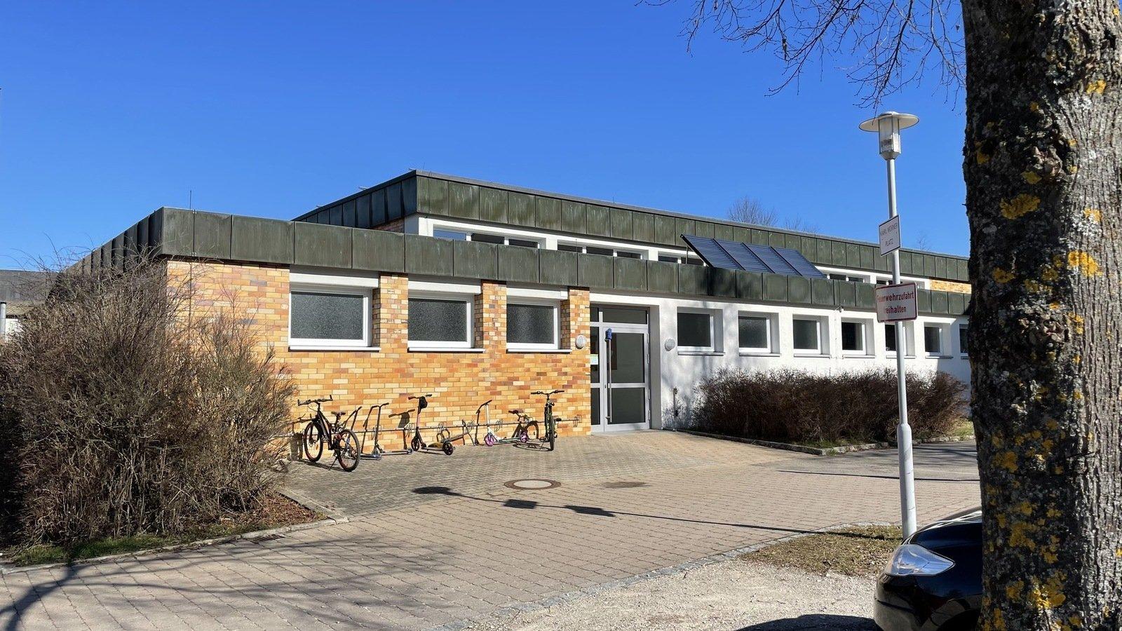 Ein großes Gebäude mit braunen Kacheln, vor dem Gebäude sind Fahrräder abgestellt