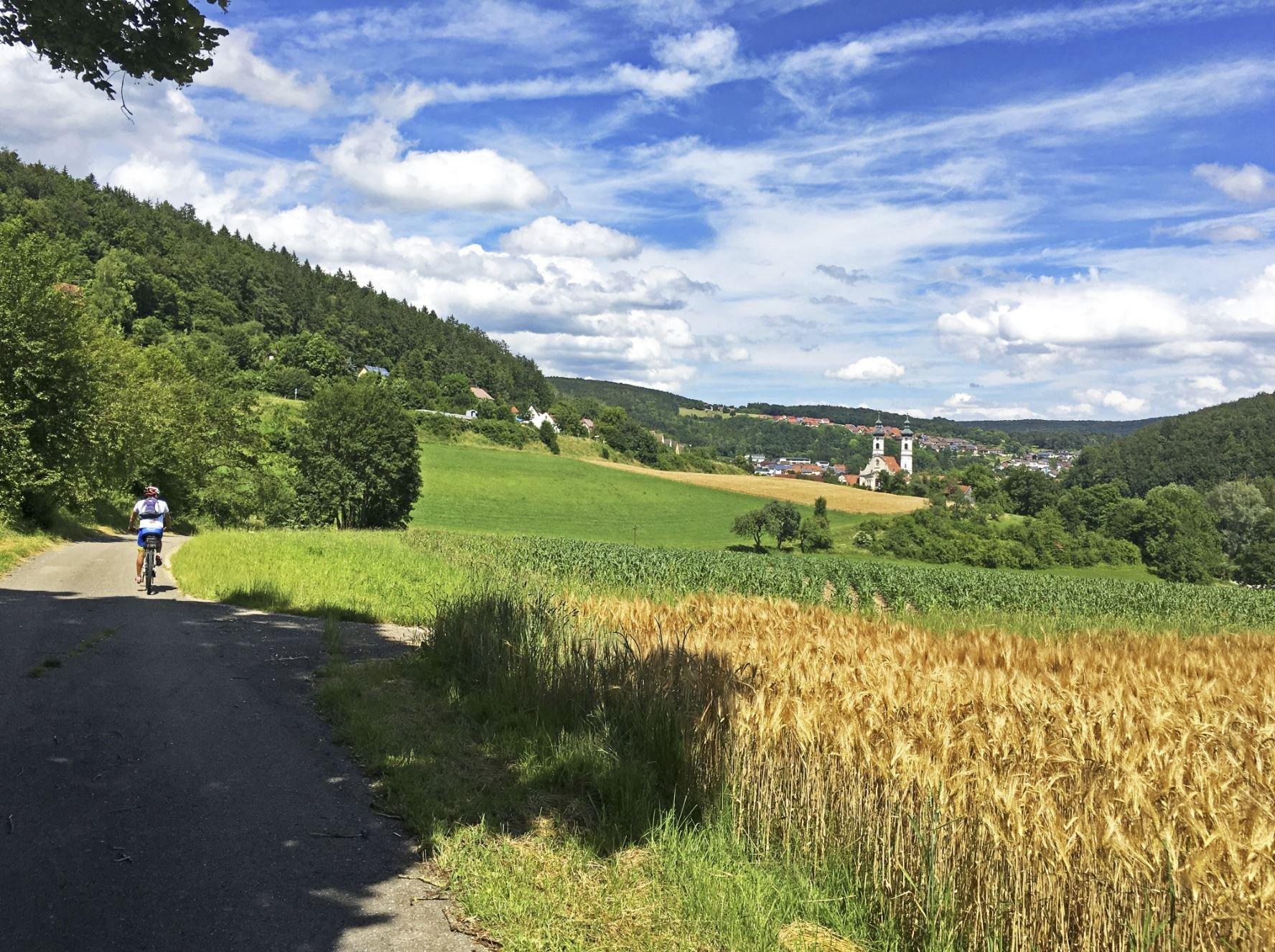 Ein*e Radfahrer*in fährt auf einem Teerweg in Richtung einer Stadt mit einer prägnanten weißen Kirche. Rechts sind Felder, links sind Sträucher. Der Himmel ist leicht bewölkt.