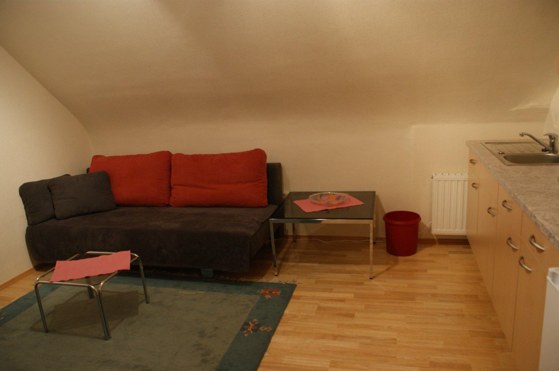 Schwarze Couch mit roten Kissen und zwei kleine Tische