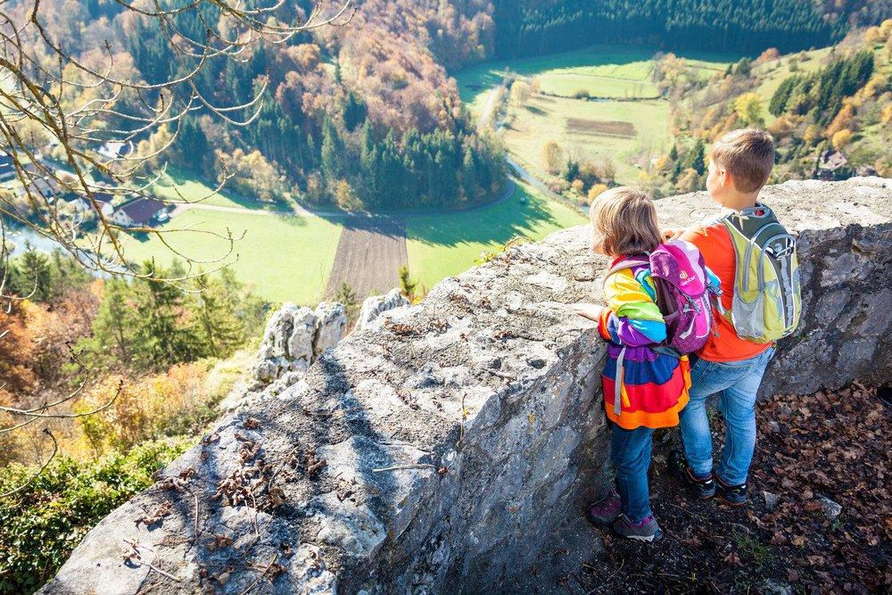 Zwei Kinder stehen an einer Steinmauer und blicken ins Tal durch das ein Fluss fließt und ein Dorf liegt. Die beiden sind bunt gekleidet und haben Rucksäcke. Es ist ein sonniger Herbsttag.