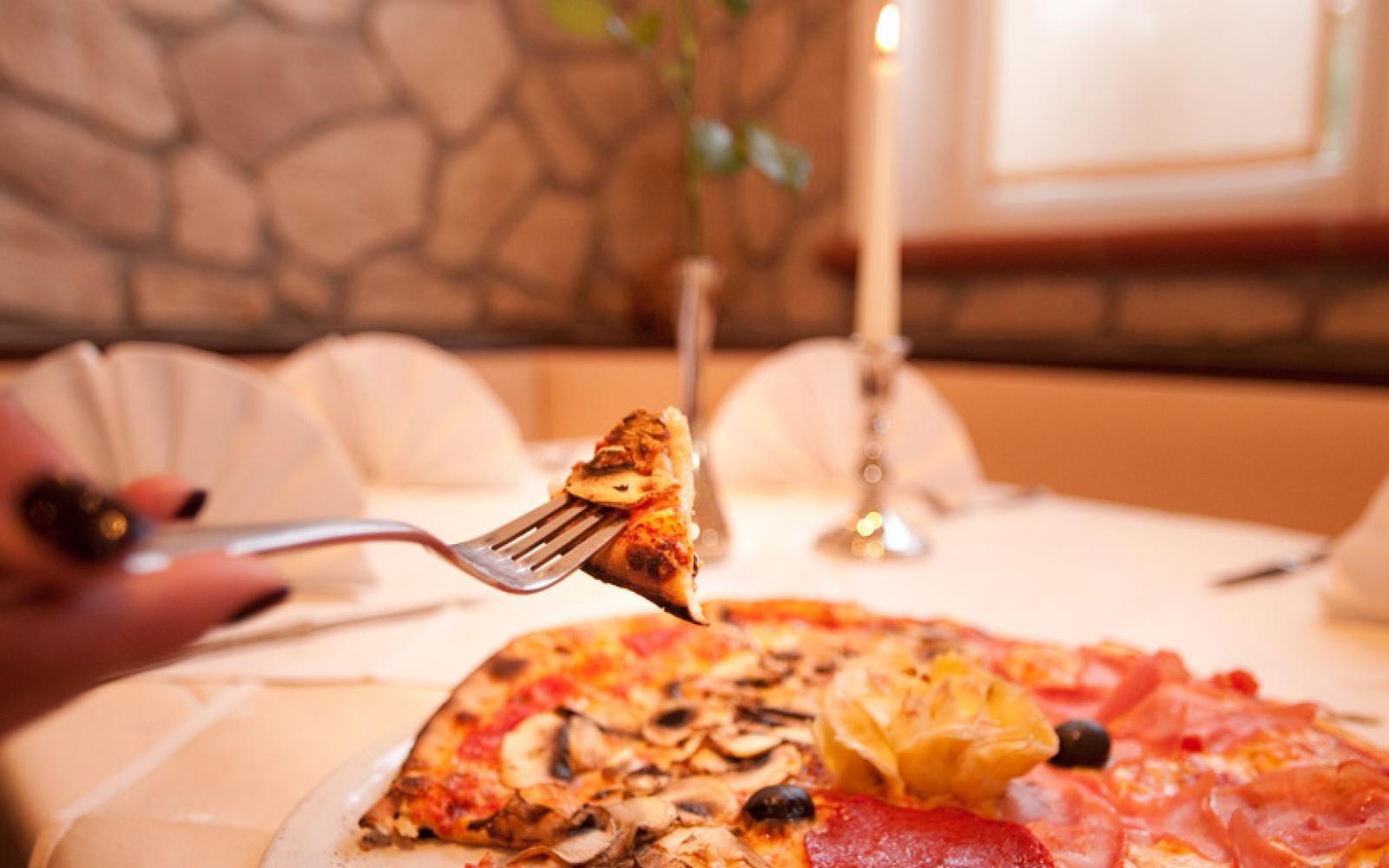 Eine Pizza auf einem Teller an einem gedeckten Tisch. Eine Hand hält ein Stück Pizza mit einer Gabel.