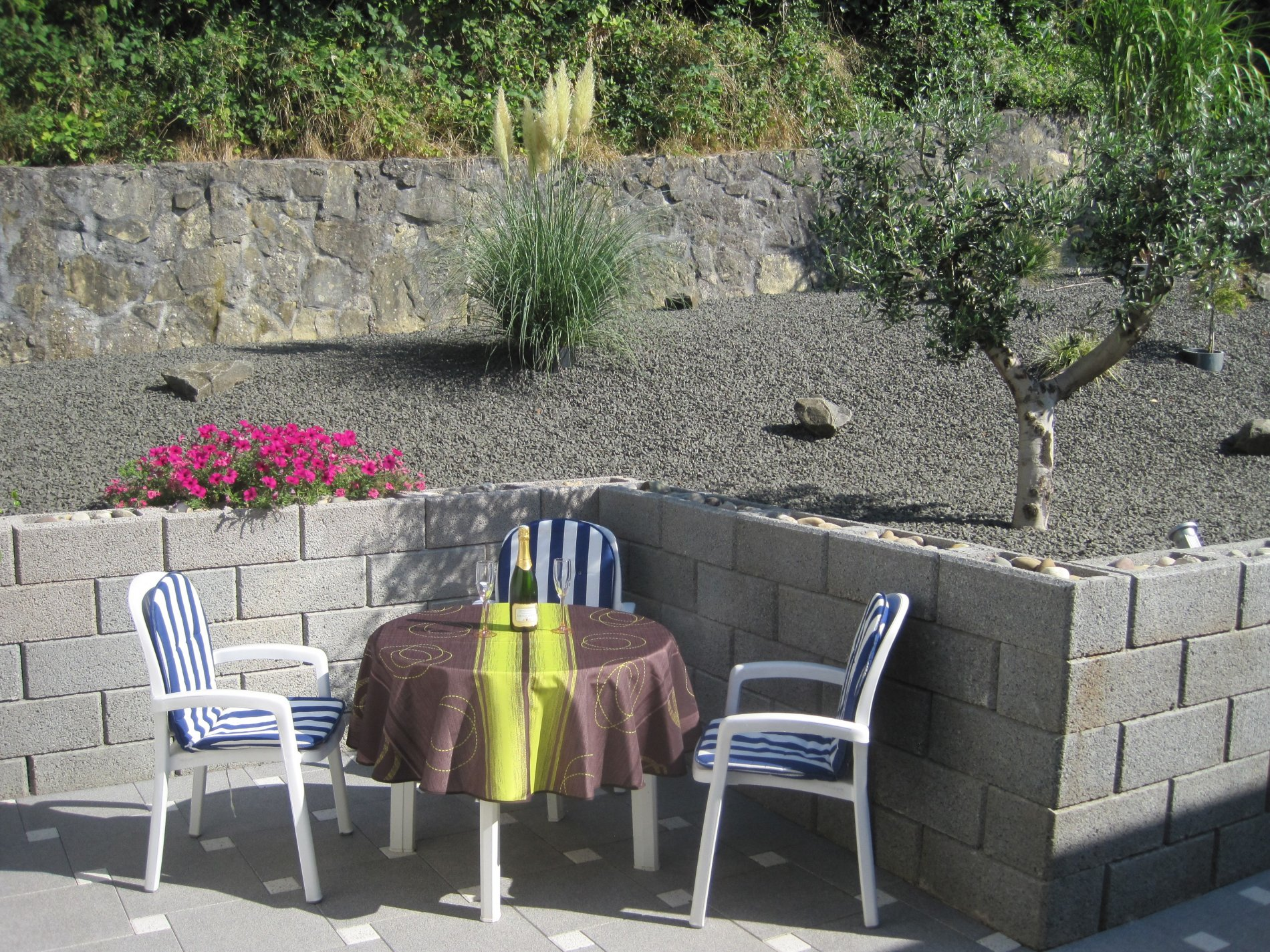 Terasse mit drei Stühlen, Tisch und Blumen
