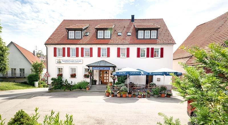 Der Gasthof zum Hirsch von außen. Ein Gebäude mit roten Fensteläden, einem überdachten Eingang und einer kleinen Terrasse mit Sitzgelegenheiten davor.