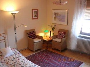 zwei Sessel mit Tisch, roter Teppich und Bett