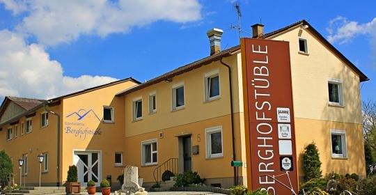 Ein orange-gelbes Haus von außen. Auf der Fassade und einem Schild steht Berghofstüble.