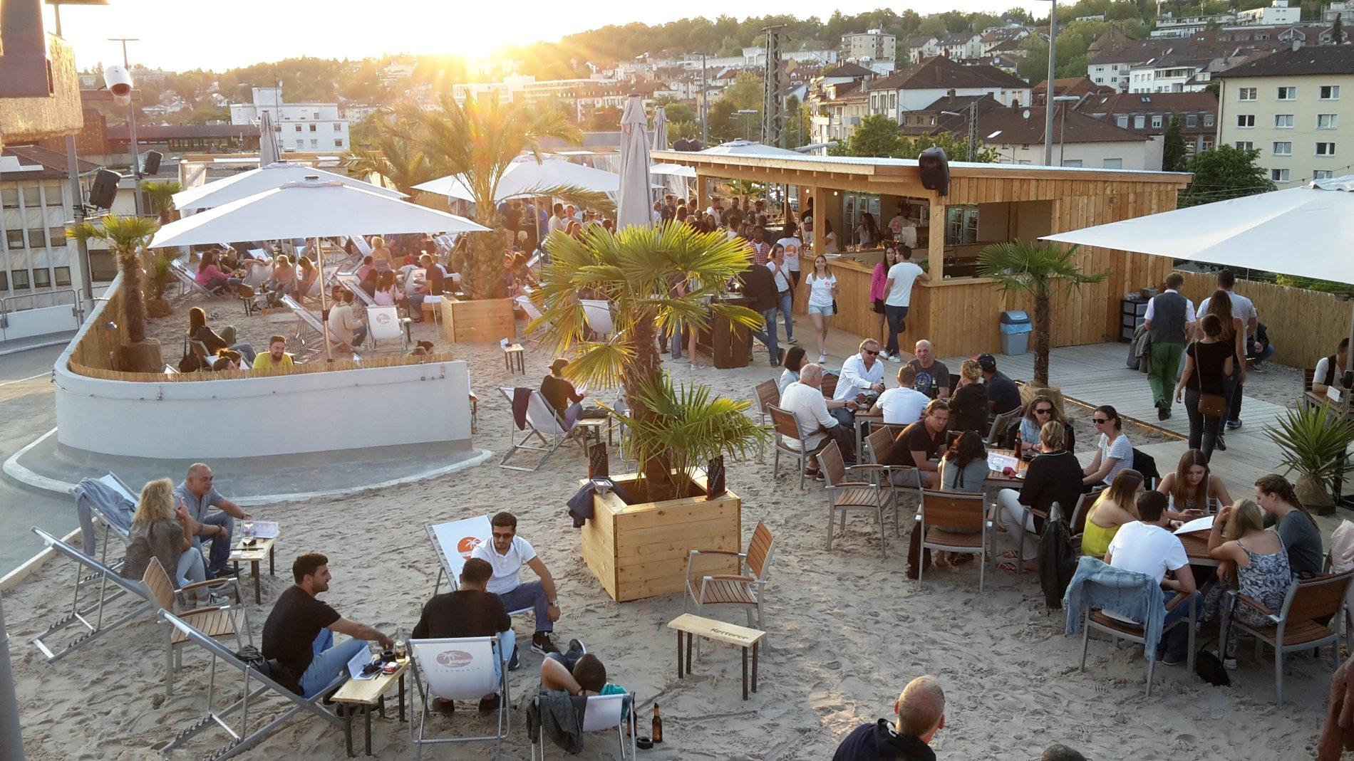 Strandbar mit Menschen auf Liegestühlen und Sitzplätzen