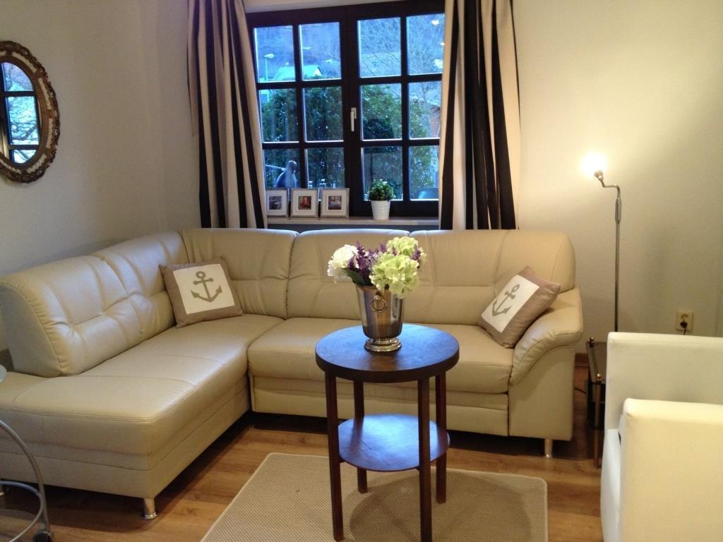 Wohnzimmer mit einer hellen Eckcouch in Leder und hellen Wänden