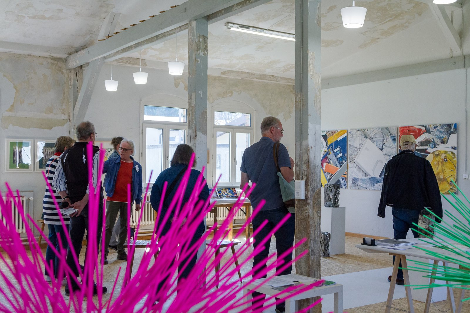 Ein weißer Fachwerk-Raum mit Personen und Bilder an den Wänden. Im Vordergrund pinke und grüne Stäbe, im Hintergrund Personen, die ein Kunstwerk an der Wand begutachten.