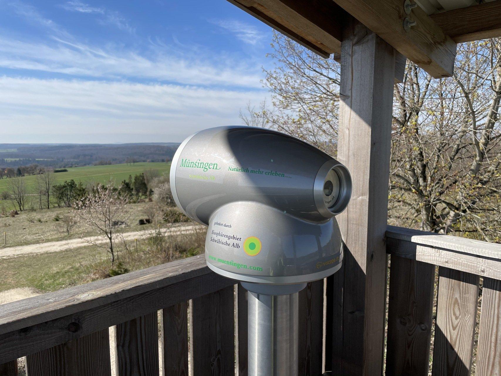 Eine Aussichtsplattform aus Holz, darauf steht ein Viscope mit grüner Aufschrift Münsingen Natürlich mehr erleben, mit Blick in die Ferne