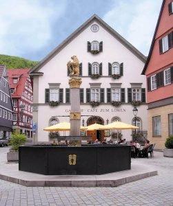 Ein Marktbrunnen auf einem Platz. Dahinter ein Haus mit Sonnenschirmen und Tischen davor.