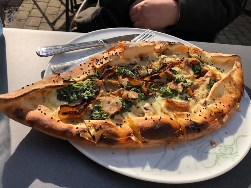 Auf einem Teller liegt ein gebackenes Fladenbrot mit Füllung aus Pilzen, etwas Spinat und Käse.