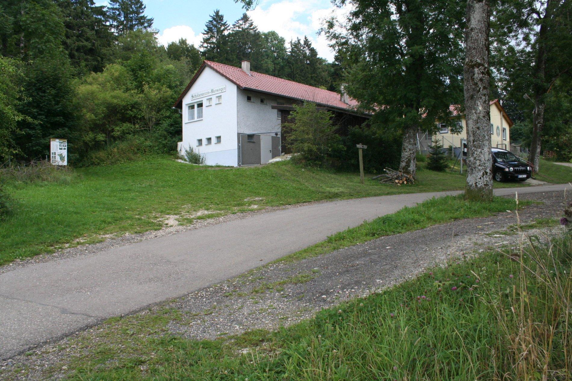 Ein Haus mit der Aufscghrift Schützenverein-Münsingen. Dahinter ist Wald, davor ist Wiese, ein paar Bäume und ein Auto.