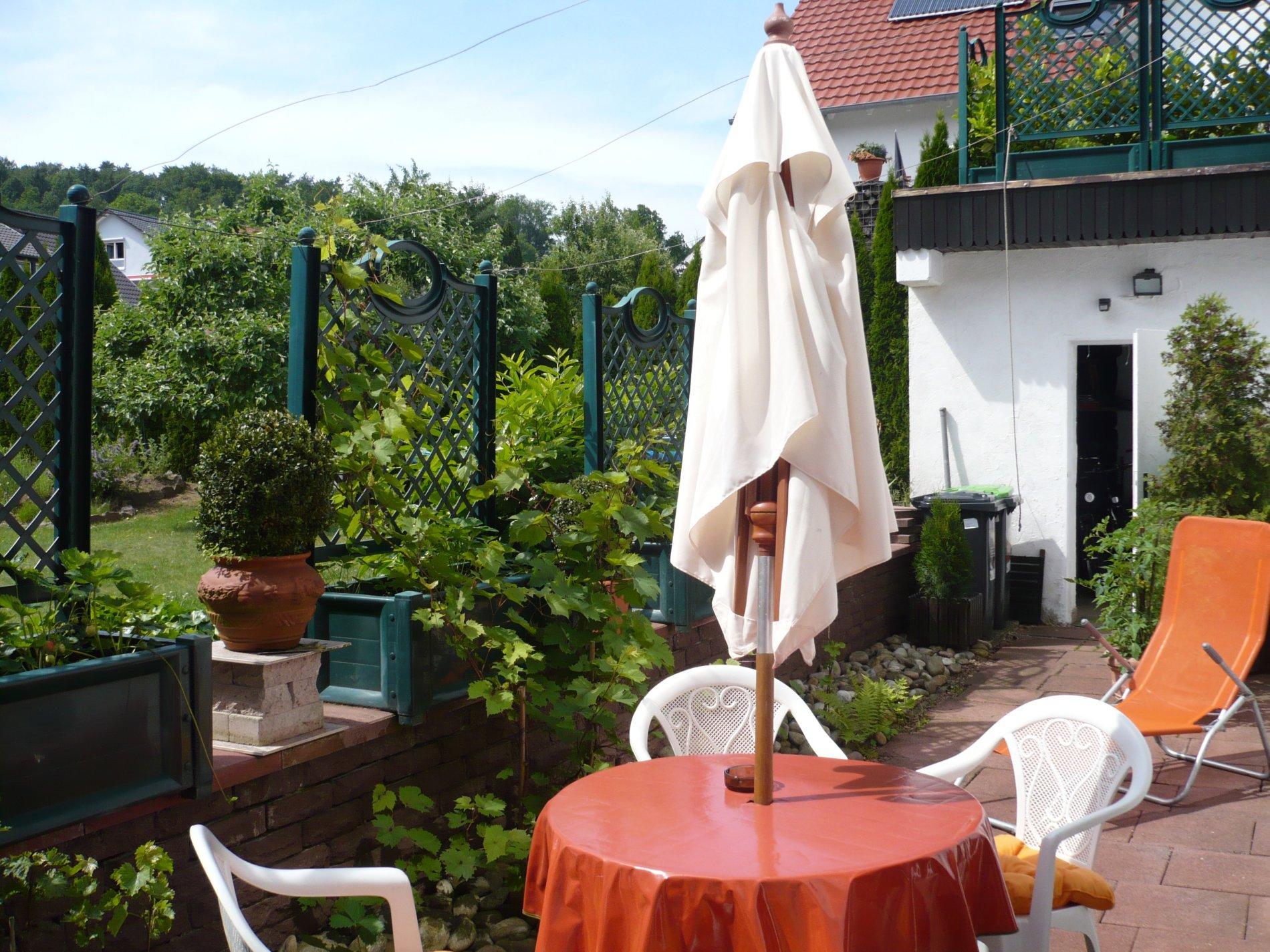 Steinterrasse mit Tisch und 3 Stühlen, Sonnenschirm und Liege und Pflanzen