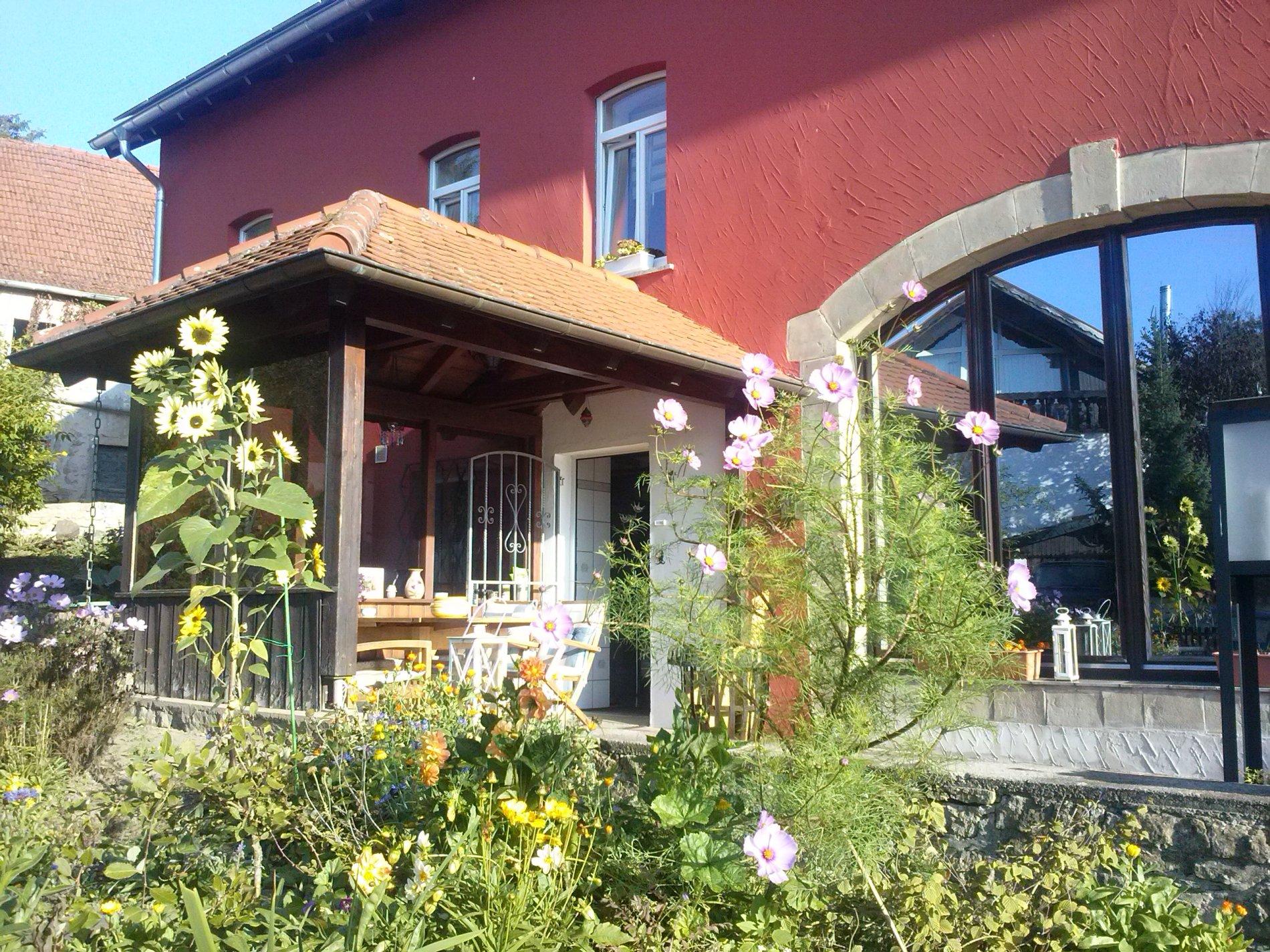 Rotes Haus mit Vordach und großem Fenster mit Terrasse und Blumen