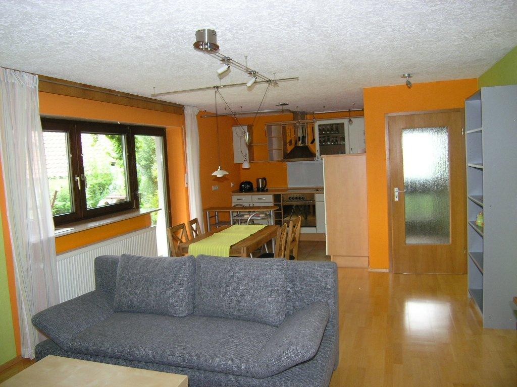 Graues Sofa mit Esstisch und 4 Stühlen und Küche auf Laminatboden