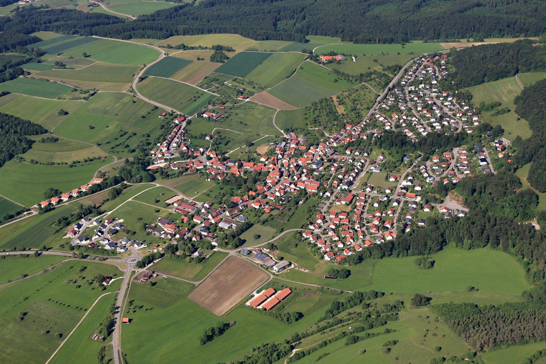 Ein Luftbild von einem Dorf. Ringsherum sind Felder und Wald.