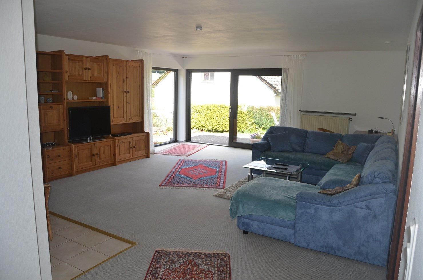 Wohnzimmer mit blauer Couch und einer Fernsehwand