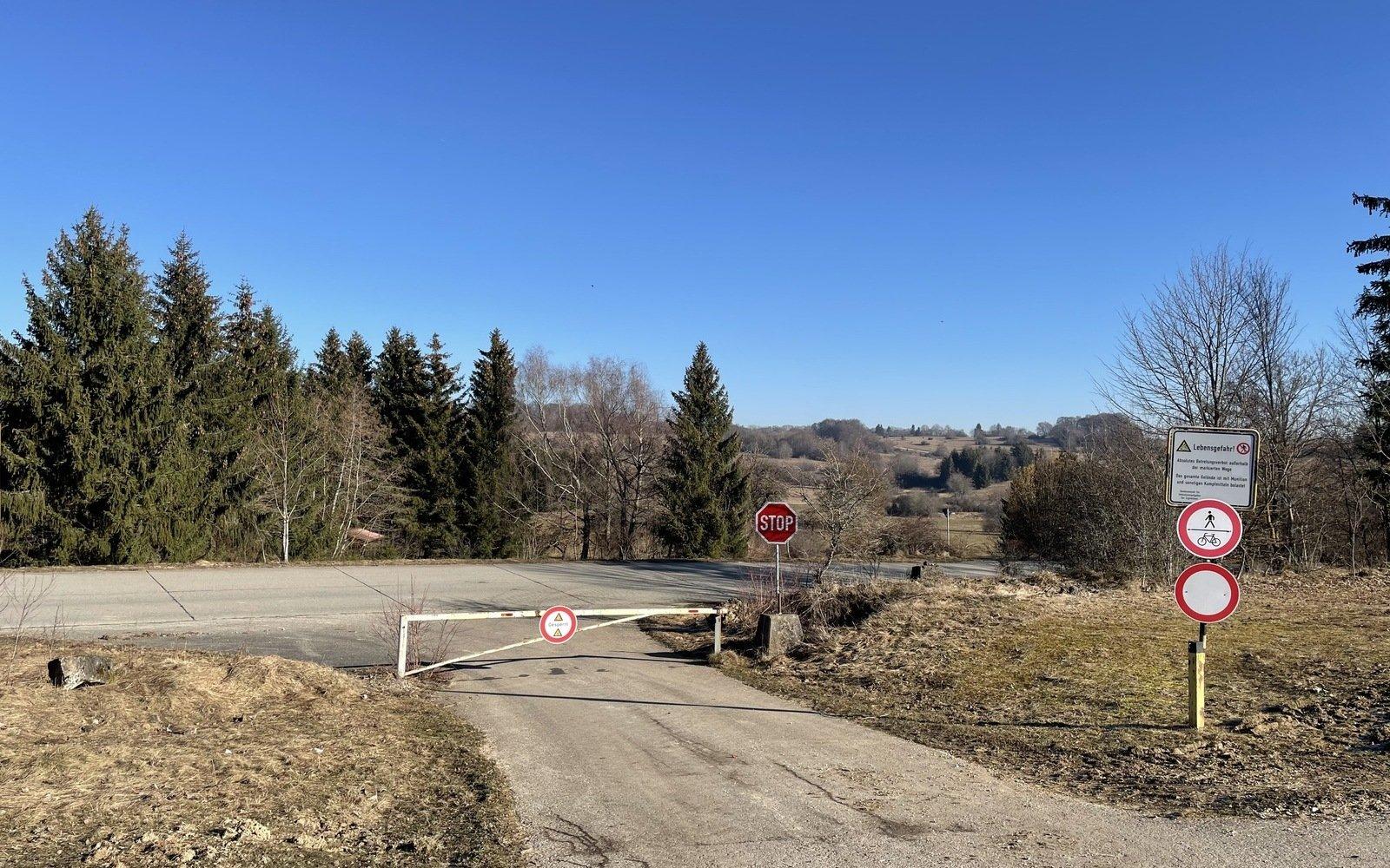 eine asphaltierte Straße mit einer Schranke und einem Verbotsschild im Hintergrund ein Wald