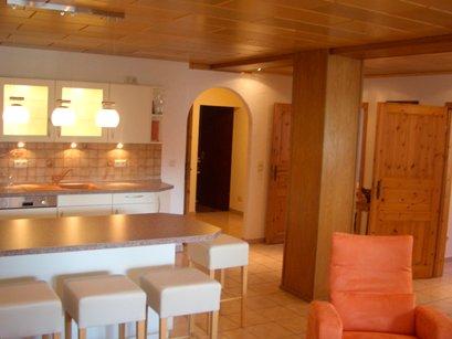 Große helle Küche mit Kücheninsel und Barhocker