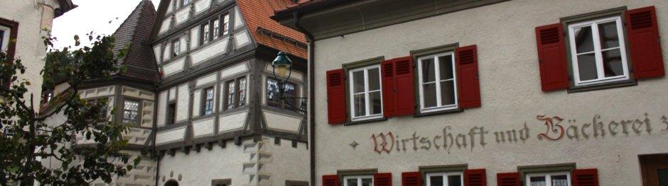 Ein altes Haus mit roten Fensterläden mit der Aufschrift Wirtschaft und Bäckerei, daneben ein Fachwerkhaus.