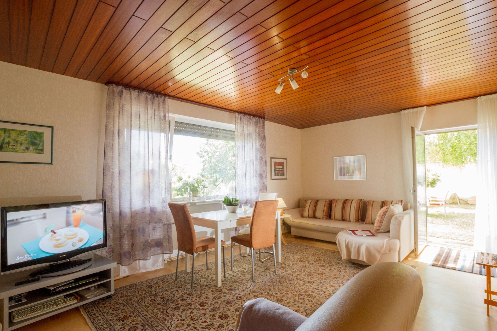 Wohnzimmer mit Couch und einen Esstisch mit zwei Stühlen