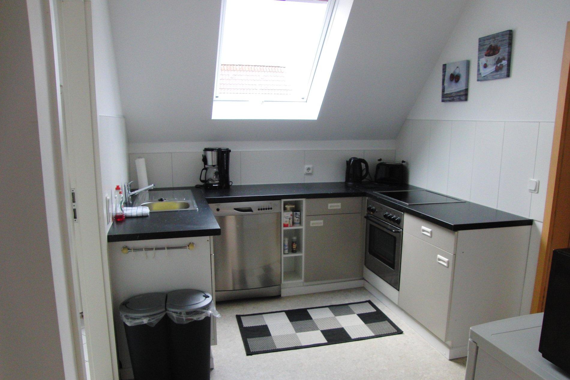 Graue Küche mit schwarzer Küchenzeile und Dachschräge