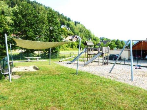 Spielplatz mit Sandkasten, Schaukel und Rutsche