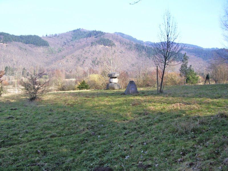 grüne Wiese mit Wald im Hintergrund, auf der Wiese stehen große, aufeinandergestapelte Steine