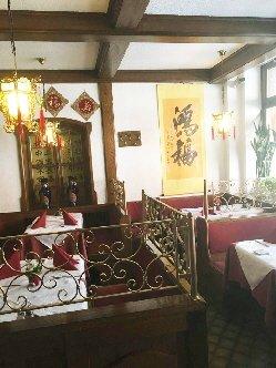 Ein Raum mit mehreren Tischen und Sitzbänken und asiatischen Dekoartikeln an den Wänden und Lampen.