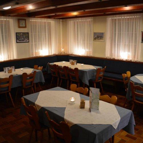 Ein Raum mit mehreren Tischen und Stühlen. Draußen ist es dunkel, vor den Fenstern hängen weiße Vorhänge, der Raum ist stimmungsvoll beleuchtet.