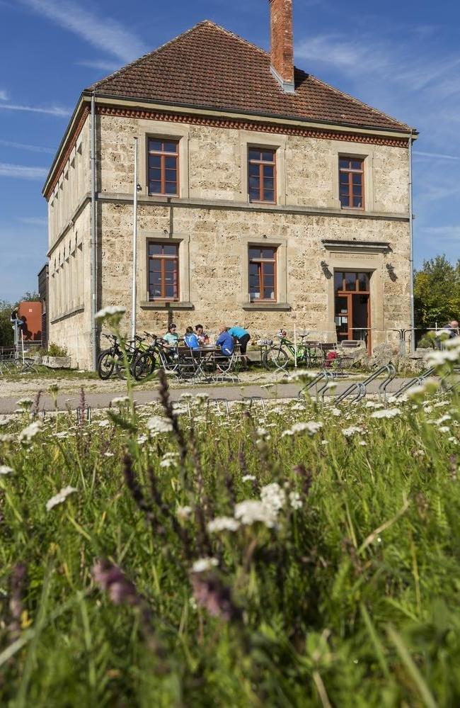 Vor einem historischen Haus stehen einige Tische und Stühle. An einem sitzt eine Gruppe, daneben angelehnt sind Fahrräder. In der unteren Bildhälfte ist eine sommerliche Blumenwiese.
