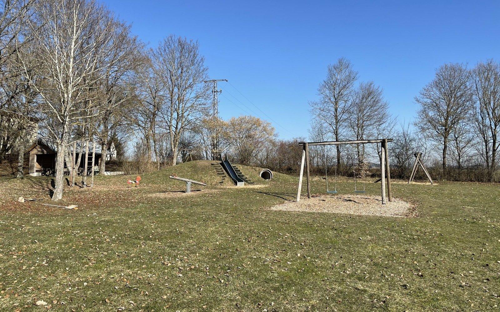 Ein Spielplatz mit einer Schaukel, einer Wippe und einer Rutsche