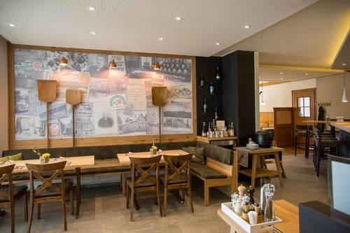Ein Raum mit mehreren Tischen und Stühlen. Er ist gemütlich eingerichtet. An der Wand hängen Bäckerschaufeln.