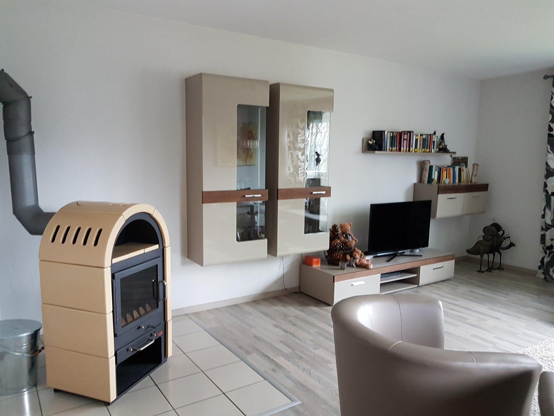 Wohnzimmer mit Kamin, Sessel, Fernseher und Wohnwnad