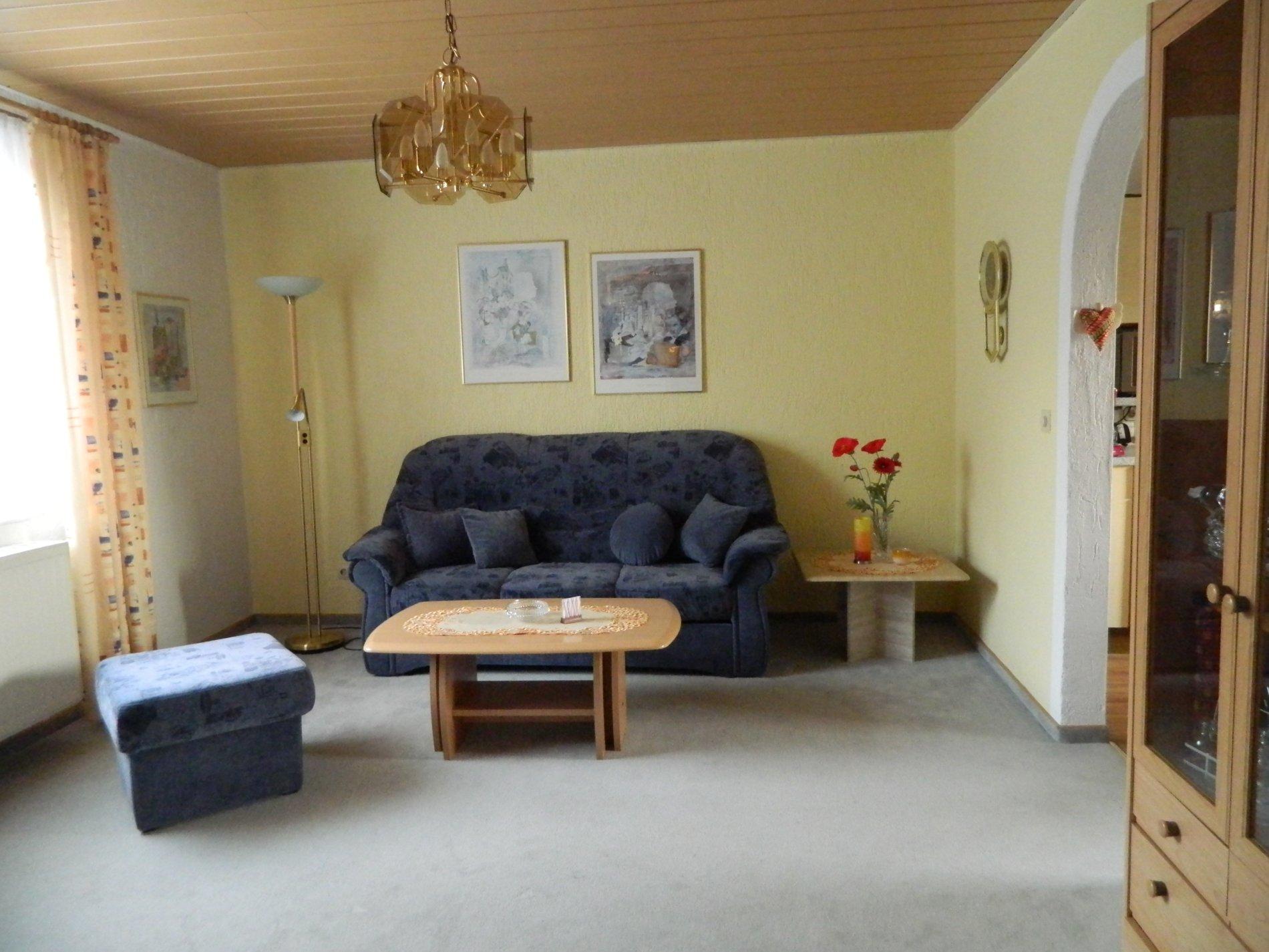 Wohnzimmer mit Sofa, Hocker, Couchtisch, Fenster und Schrank