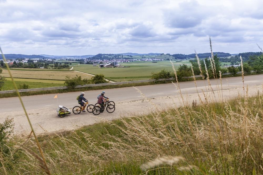 Drei Radfahrer*innen fahren mit E-Bikes auf einer Teerstraße. Im Hintergrund ist ein weiter Ausblick über Dörfer, Hügel und Felder. Ein*e Radfahrer*in zieht einen Kinderanhänger. Der Himmel ist bewölkt.